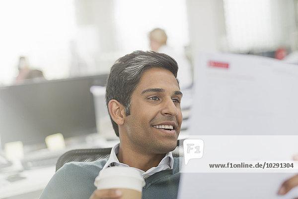 Lächelnder Geschäftsmann  der Kaffee trinkt und den Papierkram durchsieht.