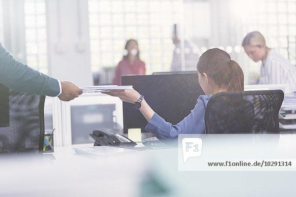 Geschäftsmann bei der Übergabe der Unterlagen an die Geschäftsfrau am Schreibtisch
