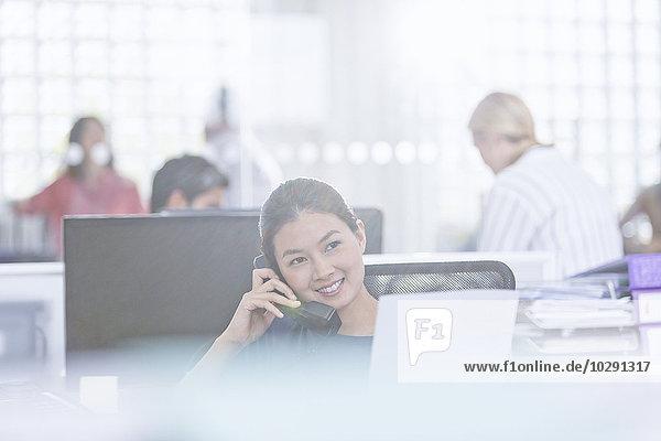 Lächelnde Geschäftsfrau am Telefon im Büro