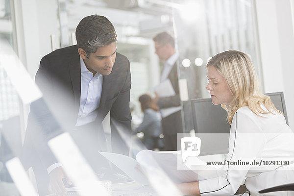 Geschäftsleute bei der Durchsicht von Unterlagen im Konferenzraum