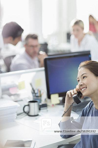 Lächelnde Geschäftsfrau beim Telefonieren am Schreibtisch im Büro