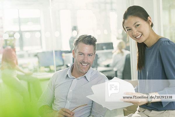 Portrait lächelnde Geschäftsleute, die den Papierkram im Büro überprüfen.