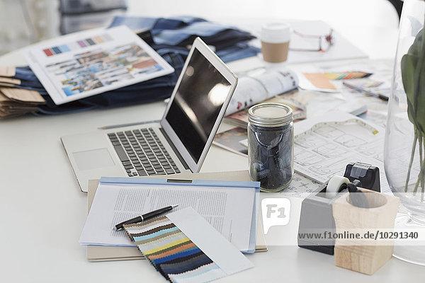 Laptop  Muster  Proofs und Papierkram auf dem Schreibtisch im Fashion Desk Office