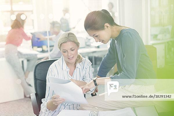 Geschäftsfrauen diskutieren Papierkram im Büro