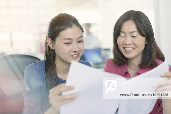 Lächelnde Geschäftsfrauen diskutieren Papierkram im Büro