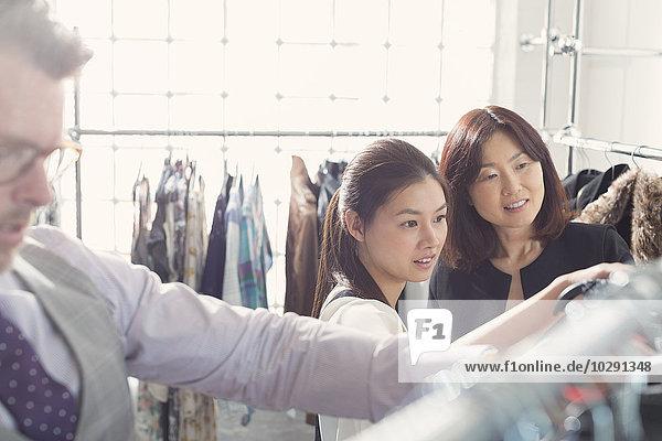Modedesigner untersuchen Kleidung auf Racks