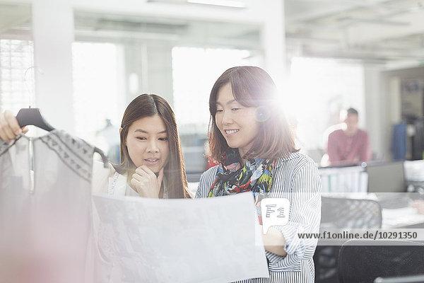 Modedesigner mit Kleidung und Nähmuster im Büro