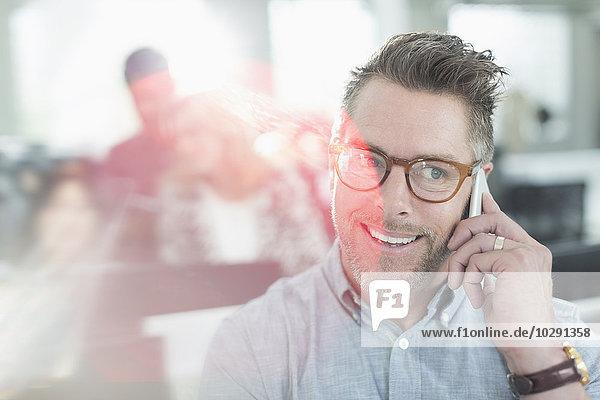 Lächelnder Geschäftsmann beim Telefonieren im Büro