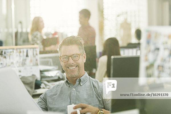 Portrait lächelnder Modedesigner beim Kaffeetrinken im Büro