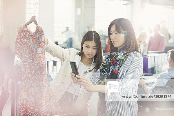 Modedesigner fotografieren Kleid mit Fotohandy