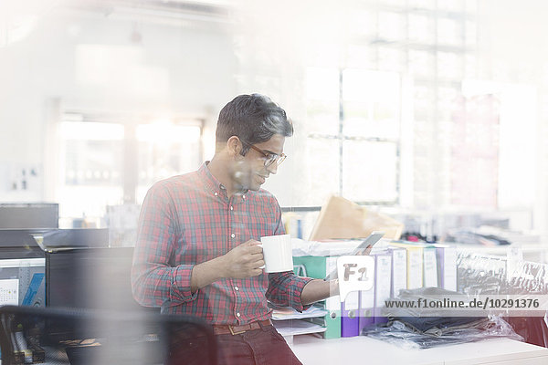 Modedesigner trinkt Kaffee mit digitalem Tablett im Büro