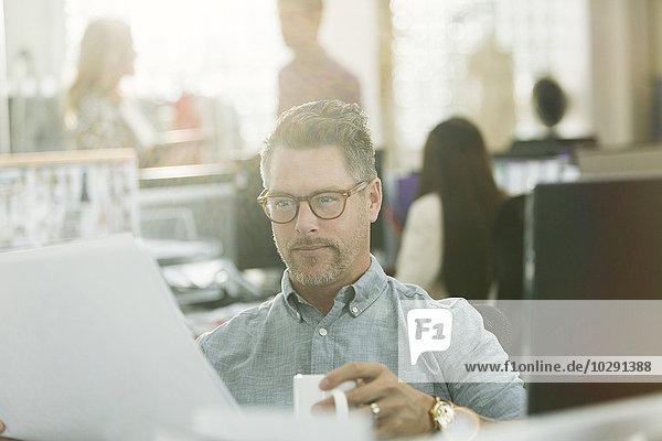 Modedesignerin bei der Überprüfung von Papierkram und Kaffeetrinken im Büro
