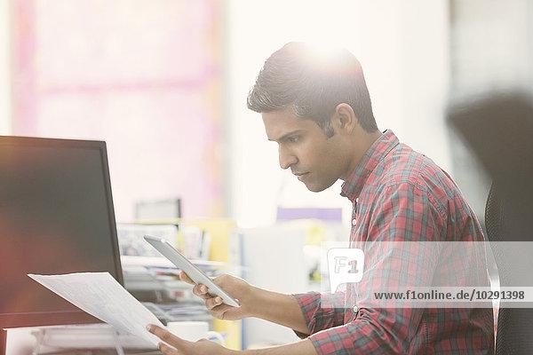 Fokussierter Geschäftsmann mit digitalem Tablett  der den Papierkram am Schreibtisch im Büro überprüft.