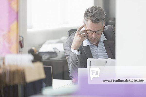 Fokussierter Geschäftsmann, der den Papierkram am Schreibtisch im Büro überprüft.