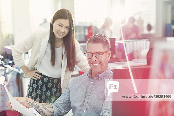 Portrait smiling fashion designers reviewing paperwork in office