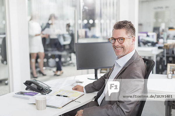 Porträt selbstbewusster Geschäftsmann am Schreibtisch im Büro