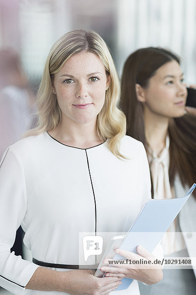 Porträtbewusste Geschäftsfrau mit Mappe und digitalem Tablett