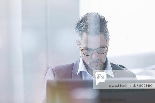 Fokussierter Geschäftsmann mit Computer im Büro