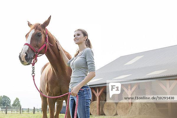 Lächelnde Frau mit Pferd außerhalb der ländlichen Scheune