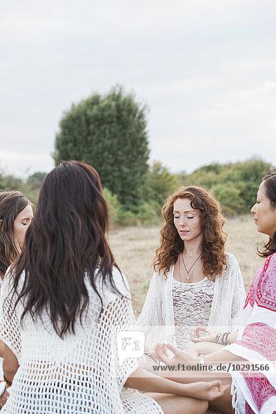 Boho Frauen meditieren im Kreis im ländlichen Raum