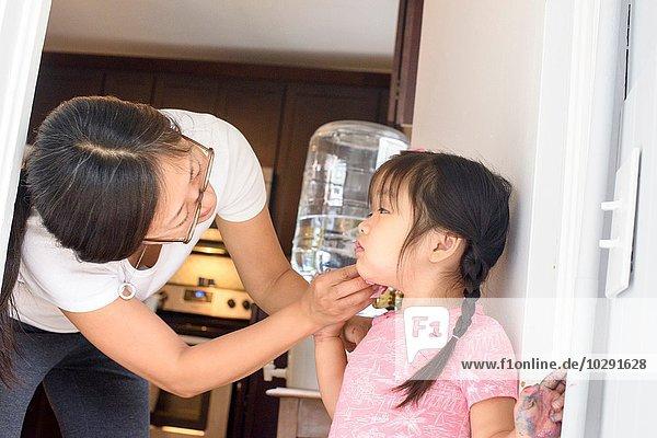 Mutter wischt das Gesicht der Tochter ab.