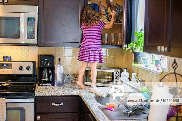 Junges Mädchen auf Küchenarbeitsplatte stehend  sucht Leckerbissen im Schrank  Rückansicht