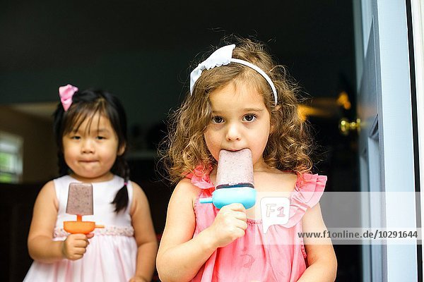 Two young girls eating ice lollies