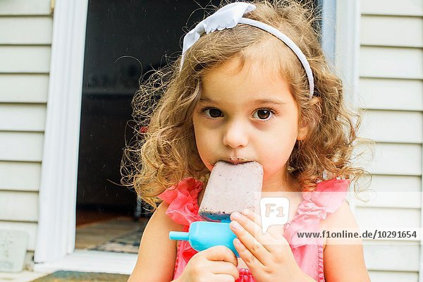 Portrait of young girl  eating ice lolly