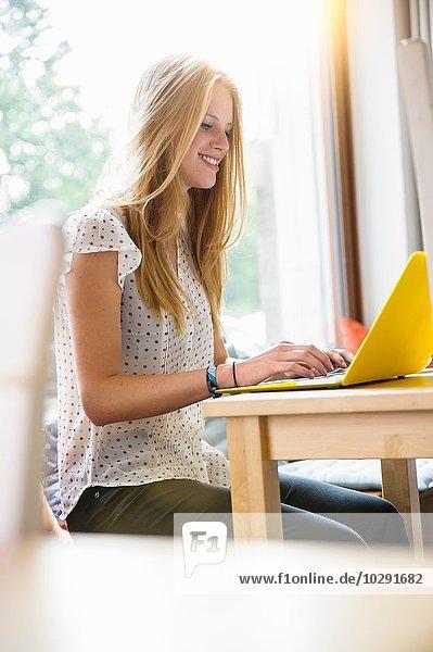 Seitenansicht der jungen Frau am Tisch sitzend mit gelbem Laptop lächelnd