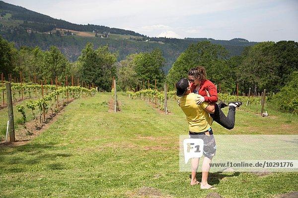 Paar umarmt im Feld  Mann hebt Frau in die Luft
