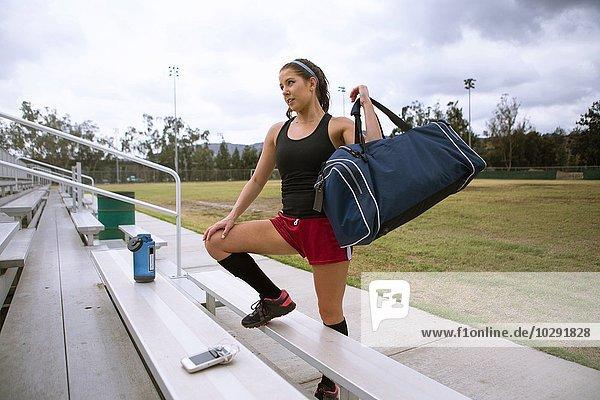 Fußballspieler stellt Sporttasche auf die Bank