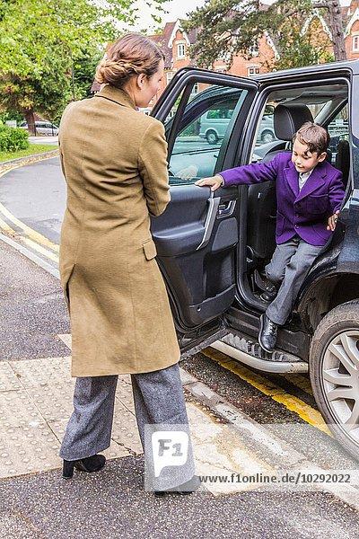 Mutter auf dem Schulweg  öffnet die Autotür für den Sohn