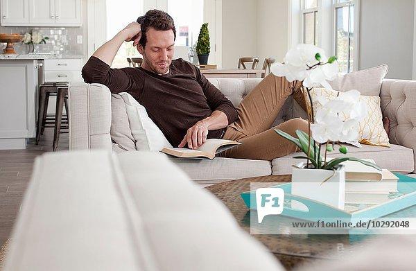 Mittlerer Erwachsener Mann entspannt zu Hause auf dem Sofa  Lesebuch
