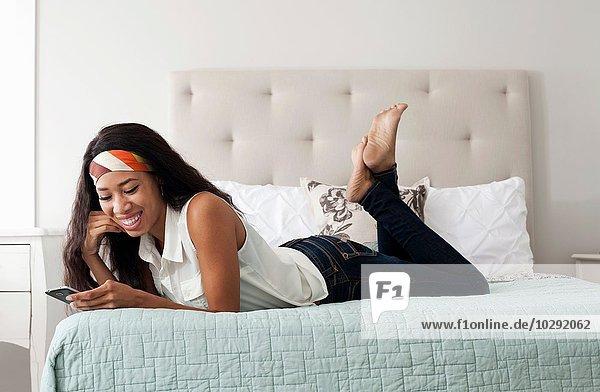 Junge Frau  entspannt im Bett  schaut auf Smartphone
