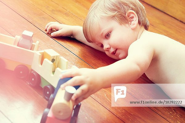 Hochwinkelansicht eines Jungen  der auf einem Holzboden liegt und mit einer Spielzeugeisenbahn spielt.