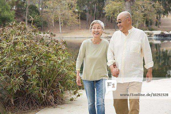 Senior couple walking along pathway  holding hands  laughing