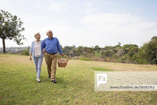 Seniorenpaar mit Arm in Arm im Park  Picknickkorb tragend