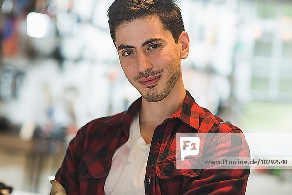 Portrait of young man wearing checked pattern shirt looking at camera smiling