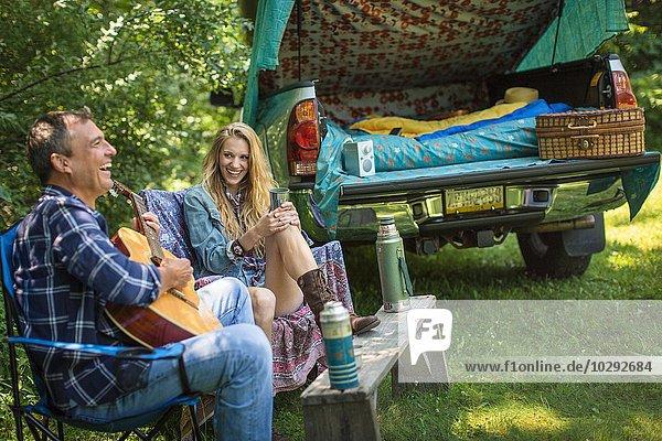 Erwachsener Mann singt und spielt Akustikgitarre für die Freundin beim Zelten.