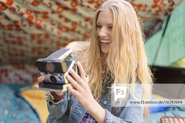 Junge Frau beim Fotografieren mit Sofortbildkamera beim Zelten