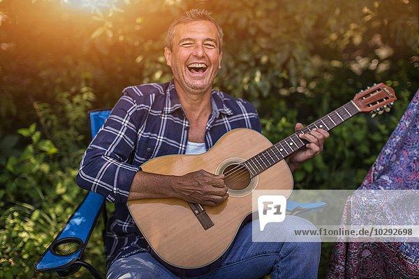 Porträt eines reifen Mannes  der beim Camping singt und Akustikgitarre spielt