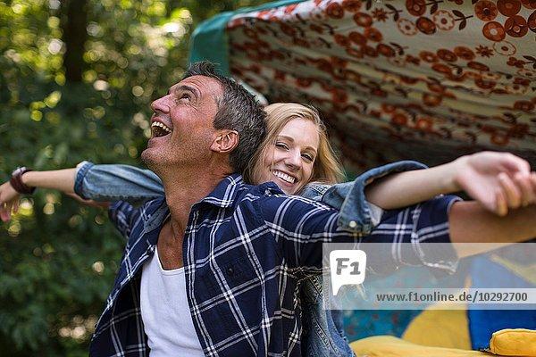 Erwachsener Mann und Freundin  die beim Zelten herumalbern.