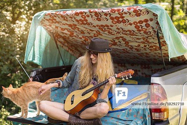Junge Frau streichelt Katze und spielt Ukulelele beim Zelten im Stiefel