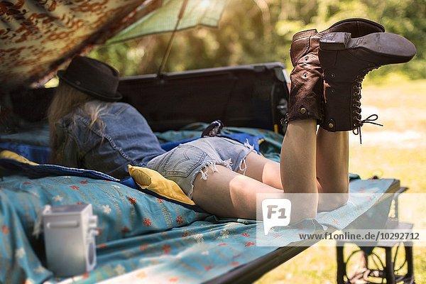 Junge Frau liegt im Kofferraum und hört Musik im Radio.
