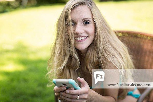 Portrait einer jungen Frau im Bikini mit Smartphone im Garten