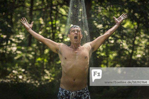 Erwachsener Mann mit offenen Armen unter der Gartendusche