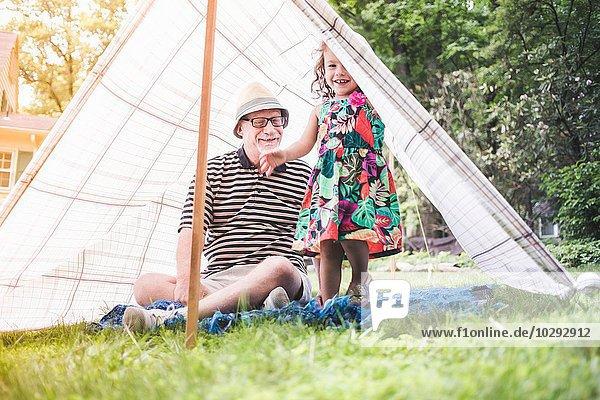 Porträt von Mädchen und Großvater beim Blick aus dem hausgemachten Gartenzelt
