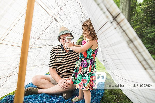 Mature man with granddaughter holding insect jar in homemade garden tent