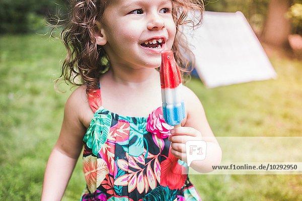 Mädchen im Garten isst Eis am Stiel