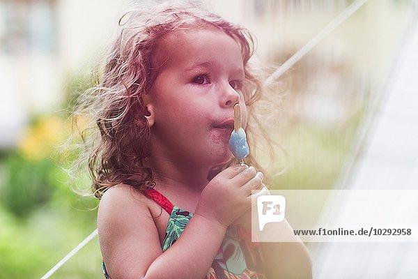 Mädchen essen schmelzendes Eis Lolly im Garten